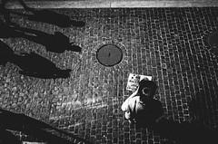 shadows in my direction (matthias hämmerly) Tags: zürich zuerich switzerland candid street streetphotography woman sun shadow reading waiting contrast grain ricoh gr black white bw monochrom monochrome city town urban cobblestones sink