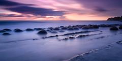 Pebbles in the Shore (Joe Azure) Tags: ca longexposure pink sunset orange seascape beach clouds landscape rocks colorful purple scenic azure cliffs epic bowlingballbeach mendo mendocinocounty coastalcalifornia roundrocks joeazure jazure mendomanmarch