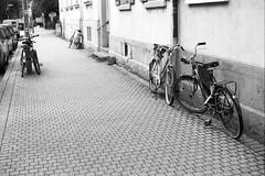 The world of bikes (Nekr0n) Tags: street leica city 2 urban blackandwhite bw film monochrome bike zeiss 35mm vintage germany t deutschland 50mm blackwhite nikon strasse rad grain streetphotography rangefinder delta ishootfilm m nostalgia negative carl stadt 100 f2 135 5000 50 freiburg schwarzweiss altstadt coolscan ilford m6 manualfocus fahrrad planar leicam6 zm ilforddelta analoge primelens strase filmisnotdead carlzeissplanart50mmf2zm imbreisgau