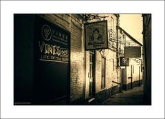 Derby alley (G. Postlethwaite esq.) Tags: derby derbyshire fujix100t vinesbar alley door monochrome photoborder signs toned