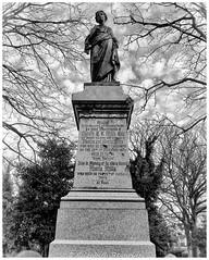 Day 60 (lizzieisdizzy) Tags: churchyard graveyard monument stone death religion name inscription homage female robes robed plinth tree trees bush bushes foliage