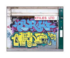 Street Art (BRK, Deno), East London, England. (Joseph O'Malley64) Tags: brk trp therollingpeople deno kr2 streetart urbanart graffiti eastlondon eastend london england uk britain british greatbritain art artists artistry artwork murals muralists writers shutter rollershutter shop shopfront sign signage awningframe cctv cctvcamera stucco stuccowork brickwork bricksmortar pointing woodenpanelling tarmac stopcocks urban urbanlandscape aerosol cans spray paint fujix accuracyprecision