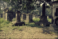 An old cemetery. (soumen19xx) Tags: trees sky india color green cemetery graveyard grass leaves yellow fauna digital photoshop canon geotagged photography eos yahoo google stem flora focus asia branch natural photos outdoor tombstone creative growth trunk historical 1855mm t3 tone chlorophyl cs3 stillphotography 1100d