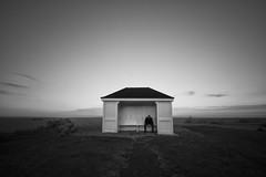 Here I am king (martinfowlie) Tags: longexposure sky blackandwhite man clouds suffolk seaside shingle loner hoodedman lmort