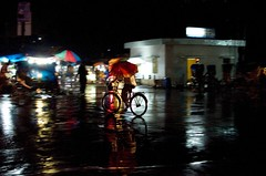 On a rainy day (night!! ) (BACHCHA POLAPINE) Tags: red motion rain night umbrella 35mm dark nikon cycle dhaka bangladesh 18g 300s motijheel d300s