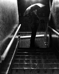 standing in the shadows (bluechameleon) Tags: city light urban bw man water rain night vancouver stairs umbrella reflections gastown blackandwhie bluechameleon sharonwish bluechameleonphotography