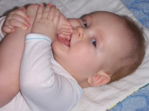 Bebe menino mordendo o pé