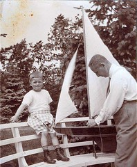 1920 man and boy with model sailboat (oldsailro) Tags: park old boy sea summer people sun lake playing man beach water pool girl sunshine youth sailboat race vintage children fun toy boat miniature wooden pond model waves sailing ship child with time yacht antique group boom regatta mast hull spectators watercraft 1920 adolescence keel fashioned