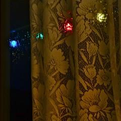 the night rain (heatherybee) Tags: nightphotography window rain night reflections lights lace curtain christmaslights raindrops colouredlights