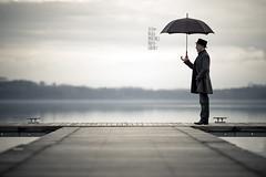 L'uomo con l'ombrello sul molo in riva al lago (Paolo Martinez) Tags: selfportrait blur hat self landscape paolo bokeh outdoor paesaggio 135mm 6d peopleenjoyingnature
