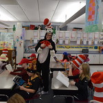 Student in Cat in the Hat costume gives thumbs up while elementary students read