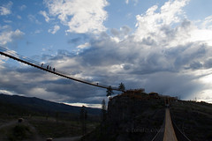 Suspension Bridge 2 (LongInt57) Tags: blue sky people woman brown white canada man mountains men clouds walking landscape person grey women bc suspension hiking okanagan gray scenic silhouettes bridges hills cables kelowna swinging canyons