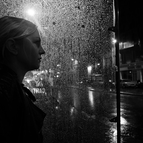 A stranger waiting for the bus on a rainy night in Paris