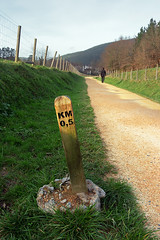 A signpost with km distance and a man walking (Mimadeo) Tags: road park wood green nature grass sign rural way walking landscape person countryside post symbol outdoor hiking path walk board direction trail arrow signpost distance information footpath signboard pathway km active