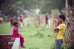 Smile, My Child ! (Sheikh Shahriar Ahmed) Tags: street film analog pose photography photo kid child phone candid streetlife fujifilm dhaka bangladesh nikonf6 fujicolorc200 dhakadivision dxonfx 55300mm dxonfilm aftabnagar epsonv330 sheikhshahriarahmed
