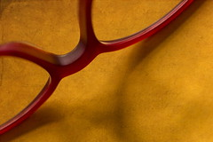 In Between - is where the nose goes (suzanne~) Tags: glasses spectacles macro red yellow texture readingglasses macromondays inbetween