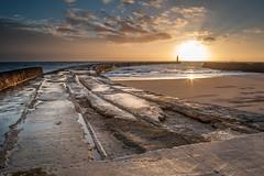 Seaham Morning (Explored) (Danny Birrell) Tags: uk light sea sky sun lighthouse seascape texture wet water clouds sunrise canon landscape coast pier day cloudy northeast canon2870 canon5dmkii vision:sunset=081 vision:clouds=0893 vision:outdoor=085 vision:sky=0815 vision:ocean=0713