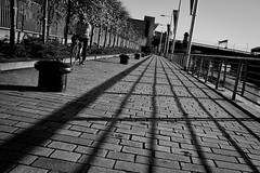 Clyde Side (Leanne Boulton) Tags: life street city light shadow people urban bw white black monochrome lines bike bicycle contrast canon river landscape scotland clyde blackwhite cityscape cyclist shadows path glasgow candid perspective scenic scene human depth leading fragment