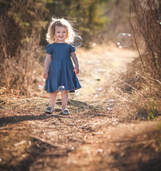Singing For Spring (davebrosha) Tags: summer portrait sun girl smile backlight children spring woods warm child purple outdoor path creative warmth sunny bubbles portraiture