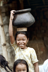 26-141 (ndpa / s. lundeen, archivist) Tags: people bali color film girl smile face smiling 35mm indonesia village child 26 nick pot southpacific balance local 1970s 1972 balancing indonesian carry carrying younggirl villager balinese dewolf oceania pacificislands nickdewolf photographbynickdewolf onherhead reel26