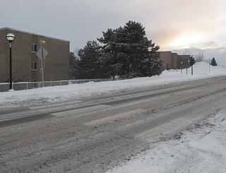 Concealment of crosswalk stripings beneath filthy gray snow.