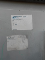 (695129) Tags: old sun west vancouver graffiti coast town washington sticker nw mail state pacific northwest label tag ripped faded wa slap usps visible priority non deteriorated bleached baked mailing remnant prioty