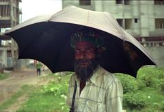 The Man Who Had Bluish Eyes... (Sheikh Shahriar Ahmed) Tags: street portrait man film umbrella beard nikon streetlife nikonfm10 fujifilm worker dhaka fm10 bangladesh 3570mmf3548 fujicolorc200 dhakadivision epsonv330 sheikhshahriarahmed