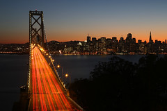 Down the Bay Bridge (AJ Brustein) Tags: ocean road street city bridge blue sunset sea urban west building water up skyline night skyscraper canon island lights oakland evening bay coast office highway san francisco long exposure cityscape view cross suspension mark top empty iii tail guard perspective trails clear level hour 5d lamps lit yerba 80 westbound lanes buena criss 5dm