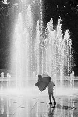 umbrellation / parasolacja (SAMO__) Tags: bw sun reflection water fountain umbrella child parasol woda soce dziecko wiato fontanna lato uwaga odbicie wiata czarnobiae odbicia patrze