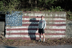 (patrickjoust) Tags: mahanoycity pennsylvania schuylkillcounty man standing portrait americanflag mural fujicagw690 kodakportra160 6x9 medium format 120 rangefinder 90mm f35 fujinon lens c41 color negative film manual focus analog mechanical patrick joust patrickjoust usa us united states north america estados unidos autaut pa small town american flag