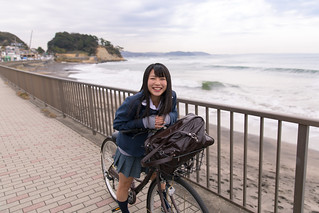 High school girl on the way to school by bicycle