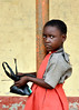 With Black Bag, Ilupeju, Lagos, Nigeria (MJ Reilly) Tags: school orange black girl outside eyes nikon play sad young lagos pole nigeria pupil nigerian d90 mjreilly ilupeju