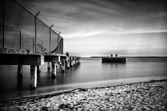 (adamwcameron) Tags: longexposure blackandwhite bw beach water clouds canon fence pier waterfront florida sigma shore nd fl t3 bocagrande weldingglass neutraldensity 1750mm