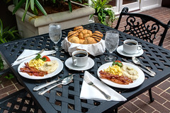 Breakfast in the courtyard at Hotel Mazarin (New Orleans Hotel Collection) Tags: food brick water glass coffee architecture breakfast tomato table hotel bacon juice chocolate napkin egg wroughtiron courtyard frenchquarter meal croissant parsley scrambledeggs