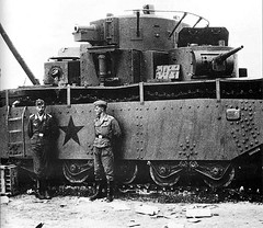 """German soldiers pose with a captured Soviet T-35 """"land battleship""""."""