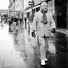 Dandy Highway Man (Leanne Boulton) Tags: life road street city light shadow portrait people urban blackandwhite bw white man motion black cold male wet monochrome face rain weather fashion composition scarf canon reflections shopping walking square mono scotland blackwhite clothing movement highway shiny faces action pavement expression glasgow candid style scene sneakers dressing pale sharp diagonal clothes suit sidewalk busy human gloves rainy shade crop portraiture bandw footpath dandy dapper