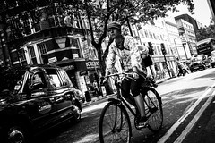 Speedy. (Tiomax80) Tags: road street city uk urban blackandwhite bw woman white black max london girl bike bicycle photography photo noir cityscape photographie cross traffic noiretblanc cab taxi centre femme nation streetphotography streetlife center scene nb line riding photograph cycle lane transportation biking londres gb charing exploration rue et fille blanc charingcross borders ville vlo urbain catel tiomax tiomax80 mcatel maxcatel tiomaxphotography