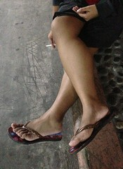 Smoking with Legs Crossed (mikeeliza) Tags: woman brown feet night asian toes hand legs skin sandals cigarette bare fingers young smoking short manila shorts filipina crossedlegs opentoed