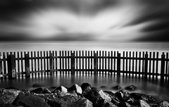 Fenced In (Lindi m) Tags: longexposure water monochrome clouds fence blackwhite rocks southwold nd110