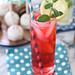 strawberry lemonade with straw and mind and ice and cake pops on polka dot napkin
