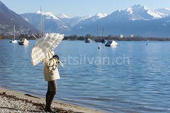 Parasol (Mats Silvan) Tags: blue sea sky people woman sunlight mountain lake snow alps color beach nature water umbrella landscape person switzerland boat ticino sand beige day transport sunny snowcapped parasol locarno lagomaggiore swissalps mountainrange standingup sailingboat lepontine