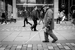 Feeling The Way (Leanne Boulton) Tags: life street old city portrait people urban blackandwhite bw white man motion black male window monochrome cane shop modern canon reflections walking mono scotland living blackwhite store movement cross blind display pavement walk glasgow candid crowd crosses pedestrian scene sidewalk busy human elderly seeing area older disabled stick visually feeling bandw juxtaposition handicap footpath less zone struggle blindness handicapped mobility reportage visibility able disability impaired bustling
