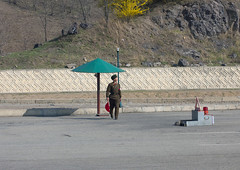 Soldier Under Umbrella At Checkpoint Pyongyang North Korea (Eric Lafforgue Photography) Tags: people horizontal umbrella asia day control military entrance police before photograph soldiers humanbeing policeman northkorea checkpoint pyongyang oneman dprk onepersononly traveldestinations northkorean colorpicture asianethnicity korea4925