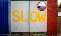 Slow (gwpics) Tags: uk blue red england english sign yellow danger warning mirror slow transport streetphotography safety signage environment