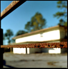 Baring my way to an empty building. (FreezerOfPhotons) Tags: bronicaectl zenzabronicaectl lomography100color unicolorc41 homecolorprocessing nikkor75mmf28forbronica rust gate ocala florida ocalafl empty outofbusiness emptybuilding sideoftheroad weeds