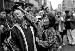 hat pull (Albert Brian) Tags: street camera nyc people newyork slr film analog 35mm photo nikon chinatown photographer candid parade filmcamera journalism nikonfe2 fe2 streetphotographer nikonlens nikonusa