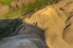 Stepping into the light (kurjuz) Tags: ghajntuffieha malta clayslopes curves green grey hiker lightandshadow lowsun undulations yellow