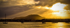 Corralejo at sunset (stumpyheaton) Tags: ocean november light sunset sea sky panorama sun seascape water silhouette yellow night clouds volcano islands boat spain nikon pano fuerteventura atlantic hills sunburst canary corralejo d5100