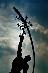 Rocket Thrower (TheMachineStops) Tags: 1992 analog film 35mmscan outdoor sculpture bronze donalddelue nyc park worldsfair 1964worldsfair flushingmeadowscoronapark queens newyorkcity silhouette sky