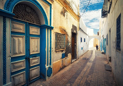 Streets of Kairouan (Philipp Klinger Photography) Tags: africa street door blue houses windows light shadow sky people sun sunlight house man streets window wall architecture clouds person hall vanishingpoint alley tunisia prayer great north mosque ar